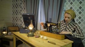 La muchacha retra hermosa de la costurera cose el paño con la máquina de coser de la vieja mano manual Mujer que trabaja en casa  almacen de video