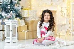 La muchacha rizada elegante vestida con placer admira luces de las guirnaldas de la Navidad del oro y decoraciones mágicas del ár Fotografía de archivo libre de regalías