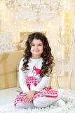 La muchacha rizada elegante vestida con placer admira luces de las guirnaldas de la Navidad del oro y decoraciones mágicas del ár Fotos de archivo