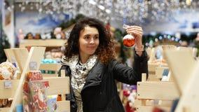 La muchacha rizada elige los juguetes de la Navidad almacen de video