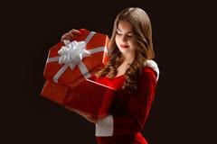 La muchacha rizada en el traje rojo abre un regalo por el Año Nuevo 2018,2019 Foto de archivo libre de regalías