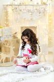 La muchacha rizada hermosa con placer admira luces mágicas de las guirnaldas de la Navidad del oro y las decoraciones del árbol q Foto de archivo