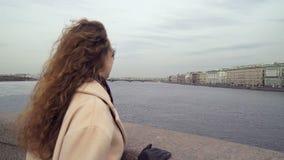La muchacha rizada joven linda mira el río metrajes
