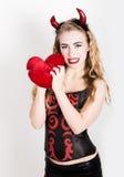 La muchacha rizada joven y hermosa con los cuernos rojos parece el diablo bonito, sosteniendo una almohada del corazón Fotografía de archivo
