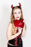 La muchacha rizada joven y hermosa con los cuernos rojos parece el diablo bonito, sosteniendo una almohada del corazón Foto de archivo