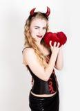 La muchacha rizada joven y hermosa con los cuernos rojos parece el diablo bonito, sosteniendo una almohada del corazón Imágenes de archivo libres de regalías