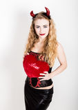 La muchacha rizada joven y hermosa con los cuernos rojos parece el diablo bonito, sosteniendo una almohada del corazón Fotos de archivo
