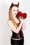 La muchacha rizada joven y hermosa con los cuernos rojos parece el diablo bonito, sosteniendo una almohada del corazón Fotos de archivo libres de regalías