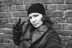 La muchacha rizado-cabelluda en un sombrero negro hace un selfie contra una pared de ladrillo, foto de la calle Imagen de archivo
