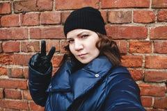 La muchacha rizado-cabelluda en un sombrero negro hace un selfie contra una pared de ladrillo, foto de la calle Foto de archivo libre de regalías