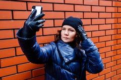 La muchacha rizado-cabelluda en un sombrero negro hace un selfie contra una pared de ladrillo, foto de la calle Fotos de archivo