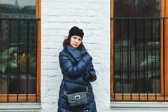 La muchacha rizado-cabelluda fotografió en la calle delante de una pared blanca entre dos ventanas Foto de archivo libre de regalías