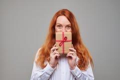 La muchacha roja contenta del pelo mira furtivamente hacia fuera la actual caja Fotos de archivo