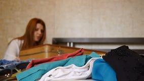 La muchacha roja del pelo est? embalando una maleta Una mujer con una maleta abierta en la cama en casa defocuse Ropa en almacen de video