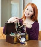 la muchacha Rojo-dirigida mira la joyería en cofre del tesoro Fotografía de archivo