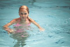 La muchacha rubia adolescente hermosa nada en una piscina Foto de archivo