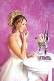 La muchacha rubia adolescente - vestido de fiesta - se sienta en la vanidad Imágenes de archivo libres de regalías