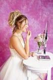 La muchacha rubia adolescente - vestido de fiesta - se sienta en la vanidad fotografía de archivo
