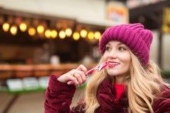 La muchacha rubia adorable en rojo hizo punto el sombrero que presentaba con el bastón de caramelo a Fotos de archivo libres de regalías