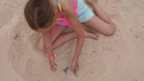 La muchacha rubia adorable encuentra la sandalia azul en la arena, visión superior metrajes