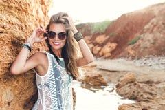 La muchacha rubia atractiva con el pelo largo est? presentando a la c?mara en fondo de las rocas Ella lleva el bikini negro bajo  imagenes de archivo