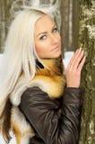 La muchacha rubia atractiva en las maderas acerca a un árbol Fotografía de archivo