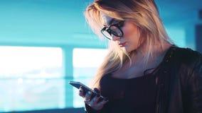 La muchacha rubia atractiva en lentes y la chaqueta de cuero utiliza su teléfono, toca su pelo, guarda en practicar surf Internet almacen de metraje de vídeo