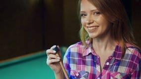 La muchacha rubia atractiva está frotando la señal con tiza almacen de video