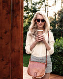 La muchacha rubia atractiva joven con el pelo largo en gafas de sol con el bolso marrón del vintage que sostiene una taza de café Fotos de archivo libres de regalías