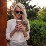 La muchacha rubia atractiva joven con el pelo largo en las gafas de sol que sostienen una taza de café tiene la diversión y buen  Imagenes de archivo