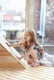 La muchacha rubia bastante pequeña se pone en cuclillas cerca de ventana grande Fotos de archivo libres de regalías