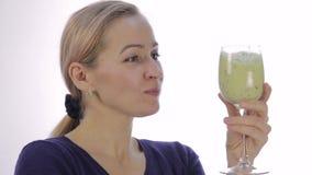 La muchacha rubia bebe el cóctel verde del detox smoothie vegetal para la aptitud y la forma de vida sana almacen de metraje de vídeo