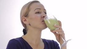 La muchacha rubia bebe el cóctel verde del detox smoothie vegetal para la aptitud y la forma de vida sana almacen de video