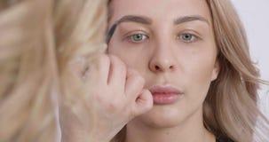 La muchacha rubia bonita consigue un maquillaje profesional de un artista de sexo femenino almacen de metraje de vídeo