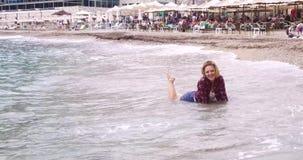 La muchacha rubia bonita en la playa del mar presenta para un fotógrafo almacen de metraje de vídeo