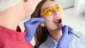 La muchacha rubia bonita en vidrios amarillos protectores en el stamotologist examinó su boca abierta El dentista de sexo femenin metrajes