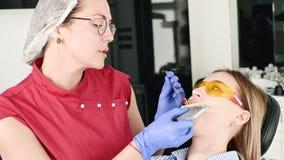 La muchacha rubia bonita en vidrios amarillos protectores en el stamotologist examin? su boca abierta El dentista de sexo femenin almacen de metraje de vídeo
