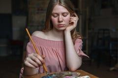La muchacha rubia bonita joven en vestido rosado descansa su cabeza en su brazo y mezcla colores con el cepillo en la paleta en e fotografía de archivo