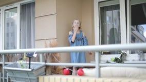 La muchacha rubia bonita se está colocando en el balcón y está enviando un beso del aire metrajes