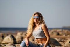 La muchacha rubia bronceada en gafas de sol y vaqueros se sienta en las rocas en la playa en un d?a soleado imagen de archivo