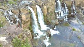 La muchacha rubia cambia actitud de la yoga en piedra por la cascada metrajes
