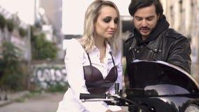 La muchacha rubia caucásica atractiva en la camisa blanca que se sienta en la motocicleta, hombre hermoso del motorista en chaque metrajes