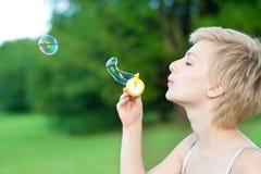 La muchacha rubia comienza burbujas de jabón Imagen de archivo libre de regalías