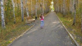 La muchacha rubia con el pelo largo corre abajo del callejón en parque del otoño Movimiento reducido de los swyings del pelo almacen de metraje de vídeo