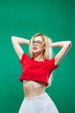 La muchacha rubia con el pelo largo y las lentes que llevan la falda blanca y el top rojo corto está presentando en estudio en fo Foto de archivo libre de regalías