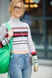 La muchacha rubia con los auriculares y la tableta está sobre el edificio Fotografía de archivo libre de regalías