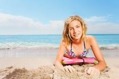 La muchacha rubia con la tabla hawaiana pone en la playa del mar Foto de archivo