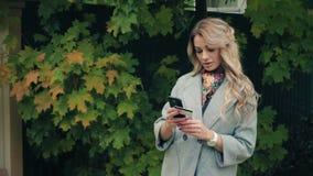 La muchacha rubia con la tarjeta del smartphone y de crédito hace compras metrajes