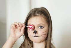 La muchacha rubia con un maquillaje que imita un gato lleva a cabo en su mano chups de un chupa imagen de archivo libre de regalías