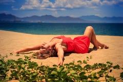 la muchacha rubia de la visión superior en mentiras rojas del vestido en la arena dobla la rodilla Fotos de archivo libres de regalías